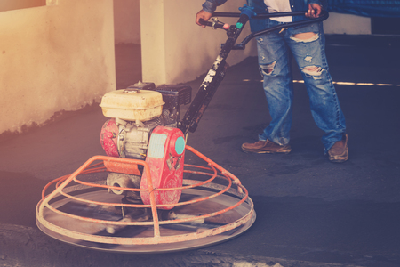 Plasterer working using scrubber machine for cement floor with vintage toned Stock Photo