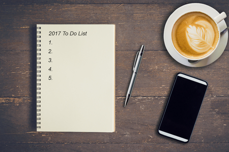 Business concept - Top view notebook writing 2017 To Do List, pen, coffee cup, and phone on wood table.