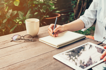 Young business woman hand with pencil writing on notebook. Woman hand with pencil writing on notebook and working at coffee shop. Standard-Bild