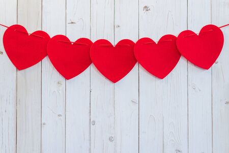 Rood hart opknoping op wit hout voor een feestje met ruimte.