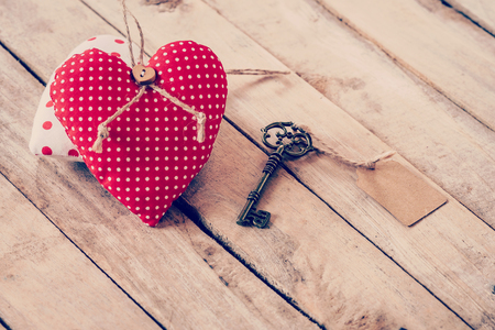 door lock love: Heart fabric and vintage key with tag on wood table background. Stock Photo