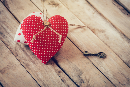door lock love: Heart fabric and vintage key on wood table background.