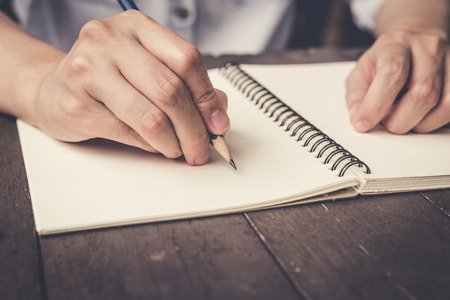 writ: close up hand woman writing notebook on wood table background. Stock Photo