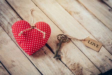 Heart fabric and vintage key with tag label LOVE on wood table background.