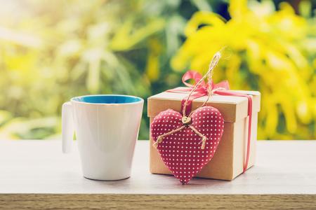 快乐的父亲节概念咖啡杯,礼盒和心在木桌上与阳光。图片