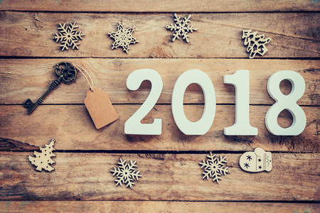 Old key with tag and wooden numbers forming the number 2018, For the new year 2018 on a rustic wooden background. Standard-Bild