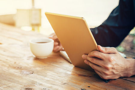 Business man using tablet on wood table in coffee shop.