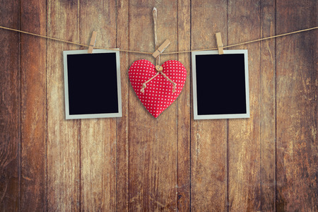 Blank instant photos and red heart hanging on wooden background.