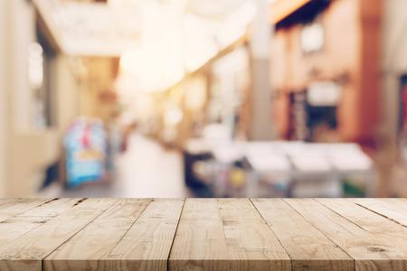 Tavolo in legno vuoto e tono vintage sfocato sfocato di persone in folla al festival di strada a piedi e al centro commerciale. Archivio Fotografico