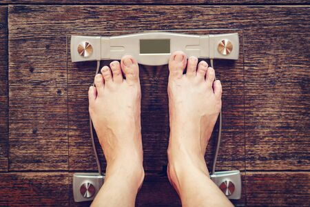 Male on weight scale on wood floor background, Diet concept.