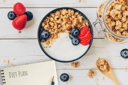 Homemade granola and fresh berries on wood table with note book and text diet plan concept, copy space. Фото со стока