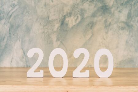 Business and design concept - wooden number 2020 for Happy new year text on wood table. Фото со стока