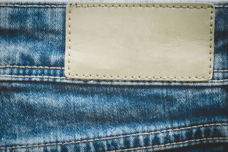 Empty leather label on jeans background with copy space Фото со стока