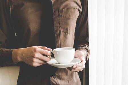 Businessman holding coffee cup at window. Creative Business Startup Idea. Фото со стока