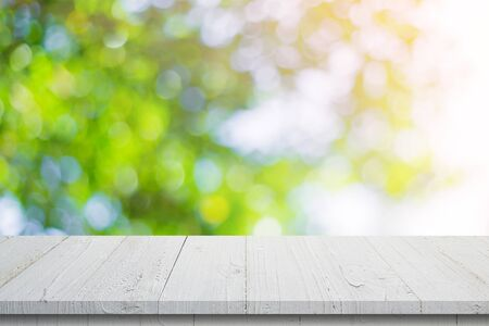 Empty wooden table and abstract blurred green bokeh leaves background texture, display montage with copy space.