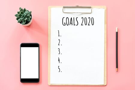 2020 New year concept. Goals list in stationery, blank clipboard, smartphone, pot plant on pink pastel color with copy space Фото со стока - 128413948