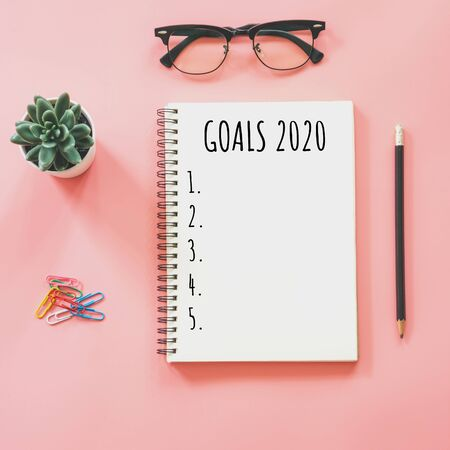2020 New year concept. Goals list in notepad, smartphone, stationery on pink pastel color with copy space Фото со стока - 128413944