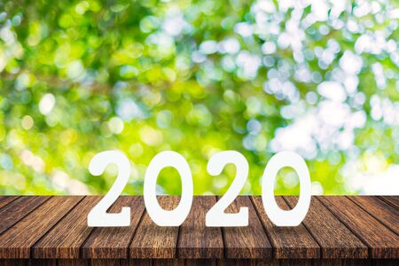 2020 New Year concept - wooden word  2020  on table and blur green light background Фото со стока