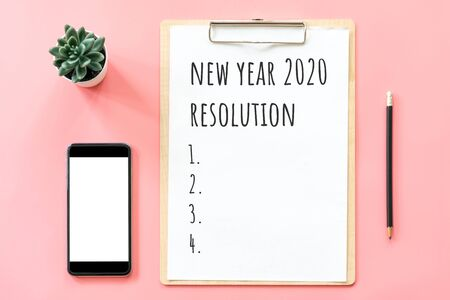 2020 New year concept. Resolution list in stationery, blank clipboard, smartphone, pot plant on pink pastel color with copy space Фото со стока