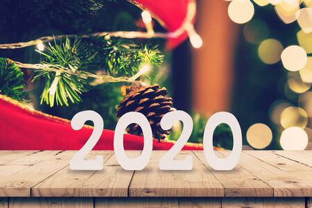 2020 New year concept on Empty wood table and christmas pine cones hanging from Christmas tree with display montage for product. Фото со стока