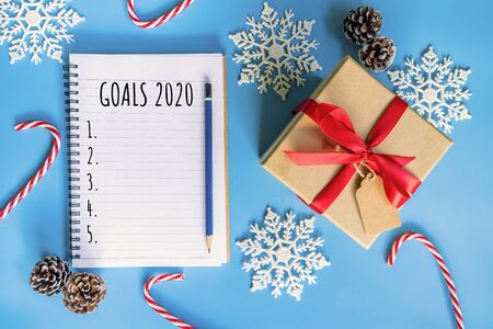 2020 New year concept. Goals 2020 list in notepad, gift box and christmas decoration on blue pastel color with copy space Фото со стока