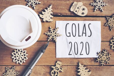 Goals for 2020 word on paper with pen and coffee cup on wooden table. Business concept.