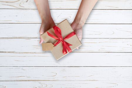 Vrouw hand met geschenkdoos op houten plank en geschilderd in witte kleur met kopieerruimte.