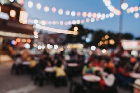 Fondo borroso en la gente del festival del mercado de la noche que camina en la carretera.