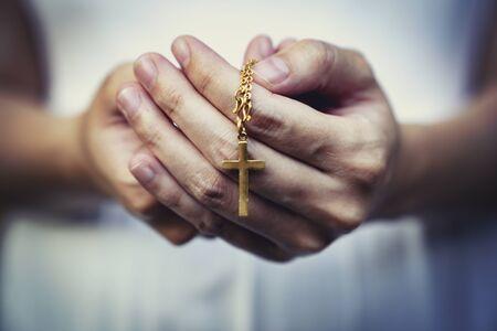 vrouw handen bidden met een kralen rozenkrans met Jezus Christus in het kruis of kruisbeeld op zwarte achtergrond.