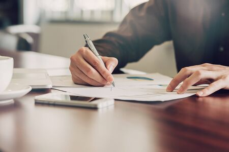 business man hand writing note paper on wooden table
