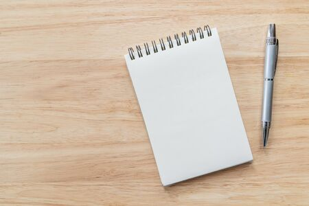 Top view of blank notebook with pen and natural light on wooden table. Stock fotó