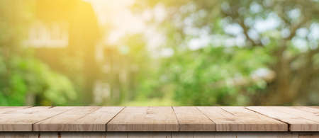 Empty wood table and defocused bokeh and blur background of garden trees with sunlight. product display template. 免版税图像