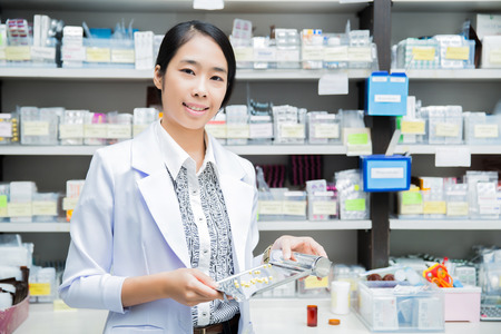 drugstore: mujeres farmacia farmacéutico verter drogas en la bandeja Foto de archivo