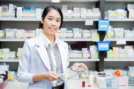 vrouwen apotheker gieten drugs in lade
