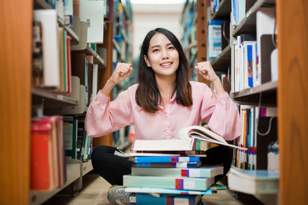 Asian female student was delighted to find the answer in the book. The University Library