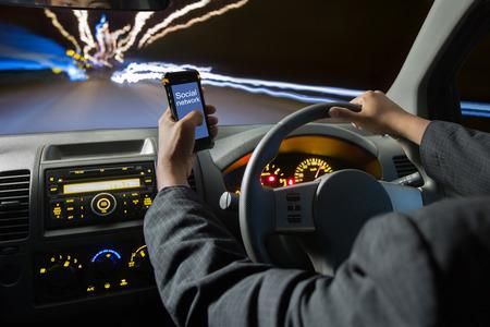 Man met behulp van slimme telefoons tijdens het rijden 's nachts, rijden op hoge snelheid Stockfoto