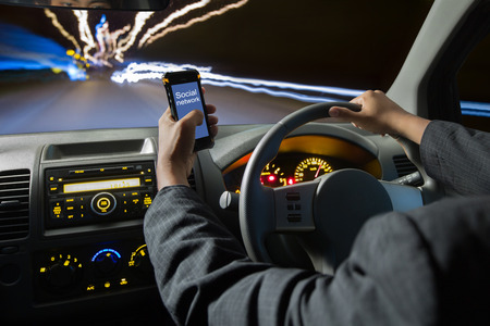 hand with phone: Man using smart phones while driving at night ,Driving at high speed Stock Photo