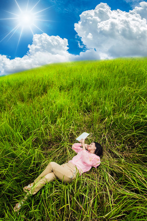 sleeping tablets: Business woman lying Tablet meadow and mountains