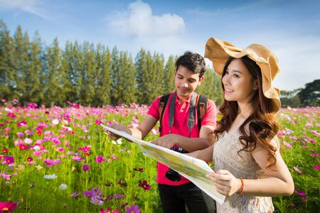 Couples traveling to Viewing Map Cosmos flowers in the garden