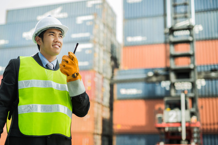 Asian Engineers are talking over the radio in shipping containers Stock Photo - 36206983