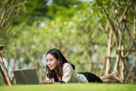 white laptop: Asian women Lying notebook computer with a smiley face Stock Photo