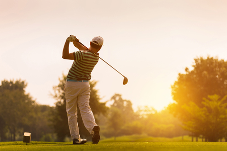 Golfers hit sweeping golf course in the summer