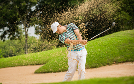 shot: The golf course is on the sand. Sand making splashes Stock Photo