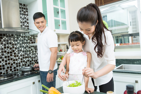 Parents are feeding their children to eat vegetables. Stockfoto