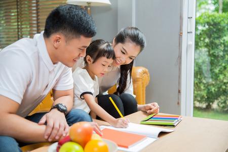Vader en moeder Onderwijs kinderen om hun huiswerk te doen thuis