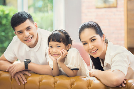 family sofa: Asian family Sitting on sofa and smiling Stock Photo