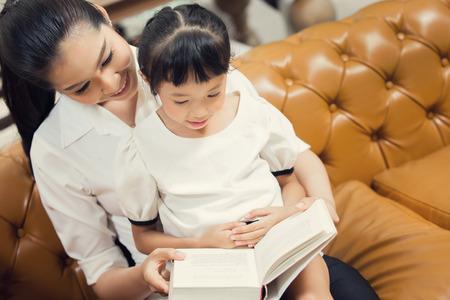 Hija de enseñanza de mamá para leer en casa Foto de archivo - 61912818