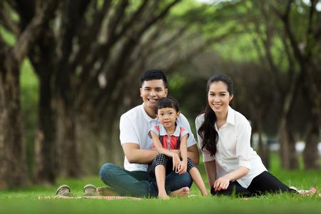 アジア系の家族は公園で座っています。幸いにも