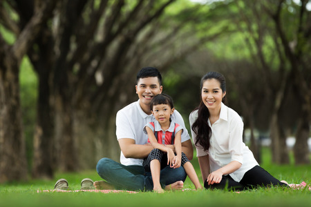 Asian family are sitting at the park. Happily