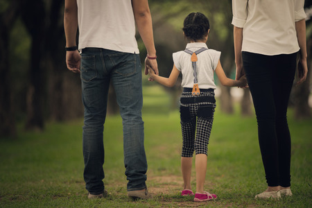 asia children: Daughters, parents were holding hands in the park Stock Photo